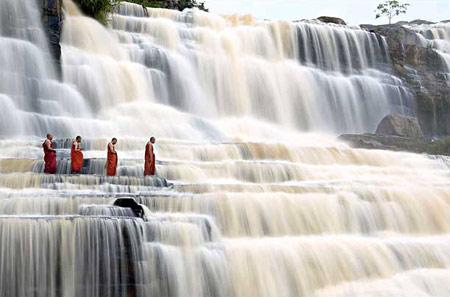 圖文:越南達拉佛教僧侶從磅古瀑布旁走過