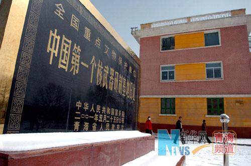 幾名當地居民經過中國第一個核武器研製基地舊址紀念碑