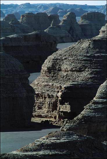 前方蒼茫的黑色戈壁中,從左至右一排排森然有序的灰藍色的雅丹,儼然一支龐大的,可以征服一切的特混艦隊,浩浩蕩蕩,氣勢磅礡地航行在波瀾壯闊的大海之上……_圖集:走近羅布泊_樂途旅遊網