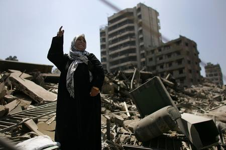 圖文:一名婦女站在被毀的家園上贊成停戰