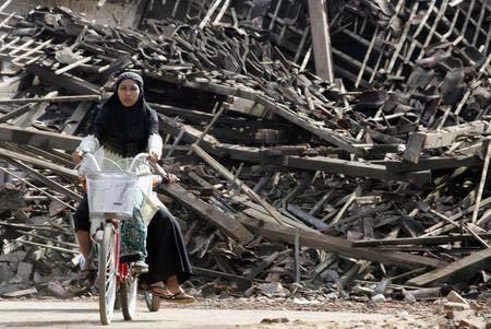 圖文:地震倖存者騎車經過一片房屋廢墟