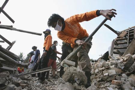 圖文:志願者在房屋廢墟中尋找遇難者