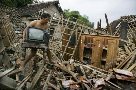 圖文:村民從被毀的家園中搬出電視機