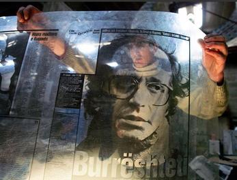 圖文:工人將前科索沃總統照片放在封面