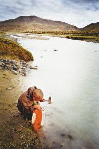 西藏阿里馬攸木拉山,在河裡取生活用水的孩子。