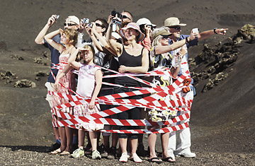 Group of tourists tied up with striped ribbon in desert