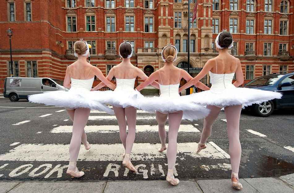 國家芭蕾舞團的舞蹈演員踩著天鵝湖中的舞步過人行道