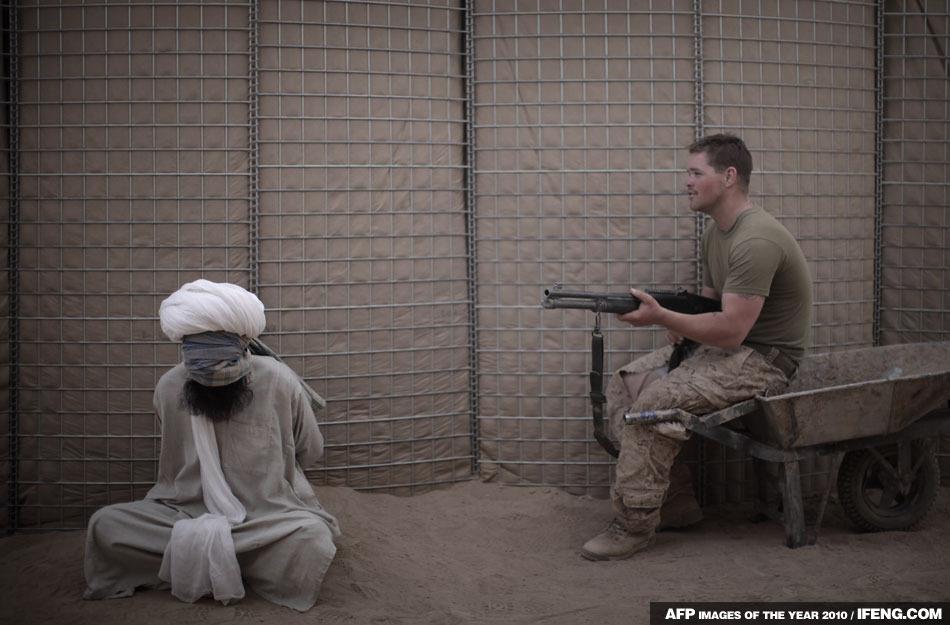 在一處爆炸現場附近,一名美國士兵在看守逮捕的男子