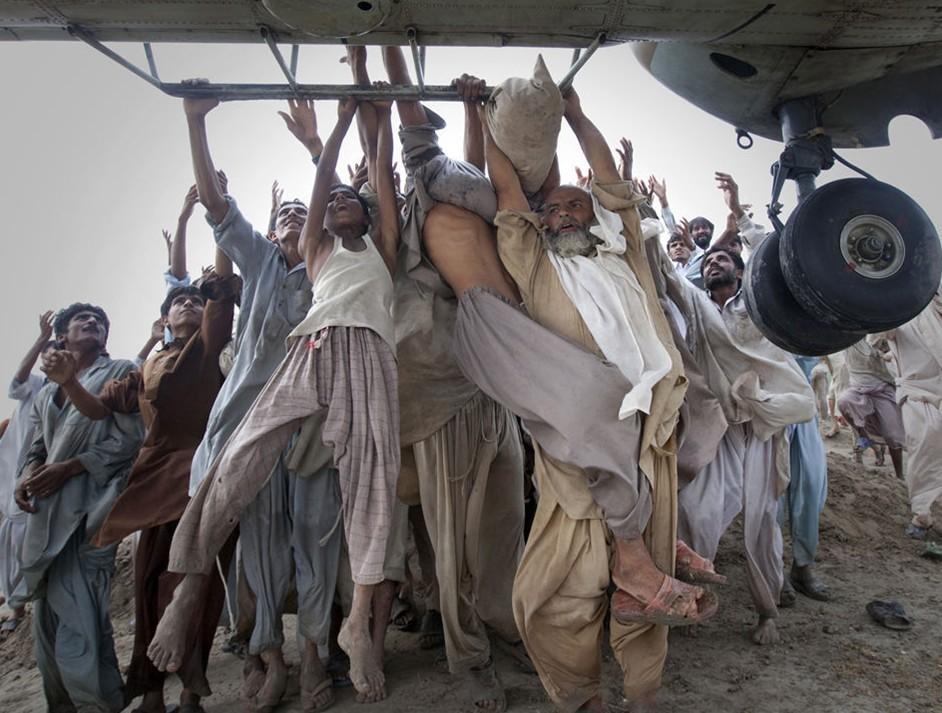 圖片:遭受洪水侵襲的巴基斯坦災民們試圖抓住運輸機