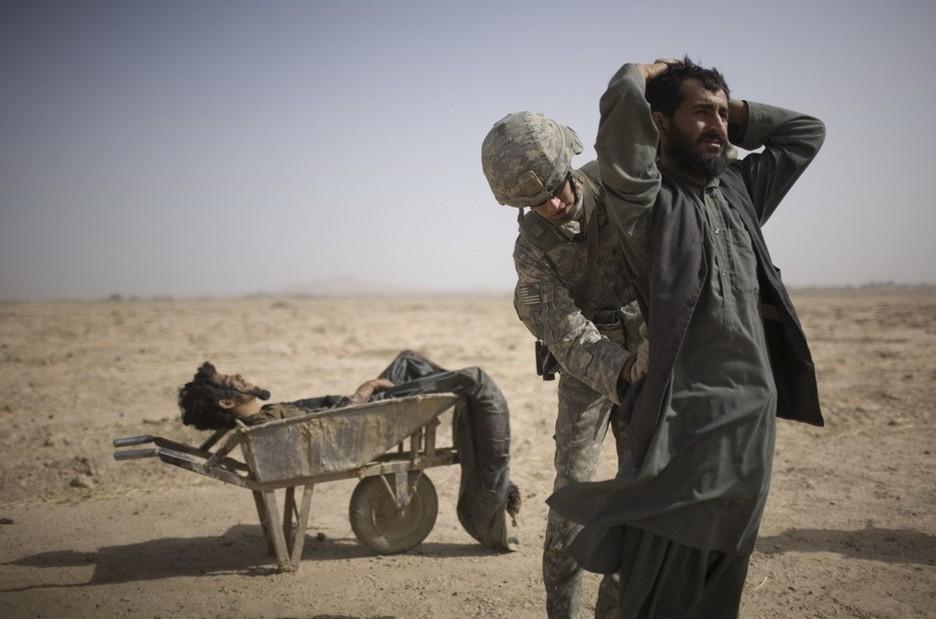 圖片:美國士兵在搜查一名塔利班簡易爆炸裝置安裝嫌疑犯的同伴