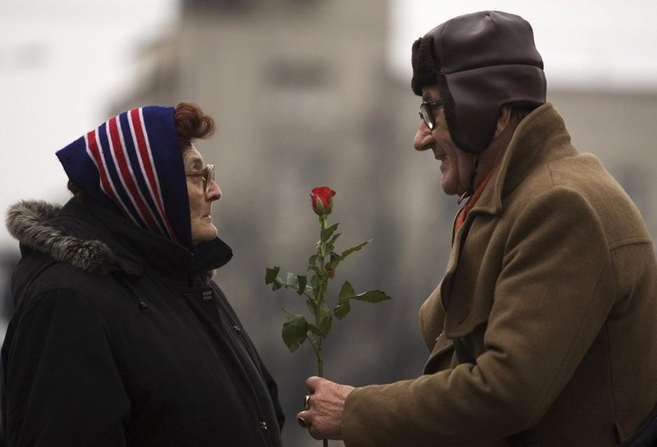 圖片:一名男子在國際婦女節這天把一枝玫瑰花送給一位女性